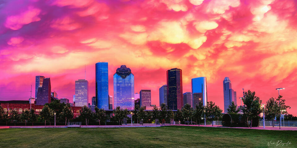 Pink, purple, and orange sunset with clouds overlooking the downtown Houston skyline.